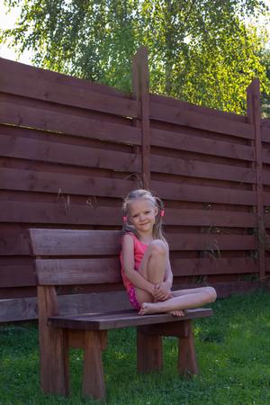 Foto de thoughtful girl sitting on a wooden bench - Imagen libre de derechos