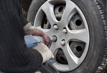 Photo pour technician unscrews nuts on a wheel with a pneumatic screwdriver - image libre de droit