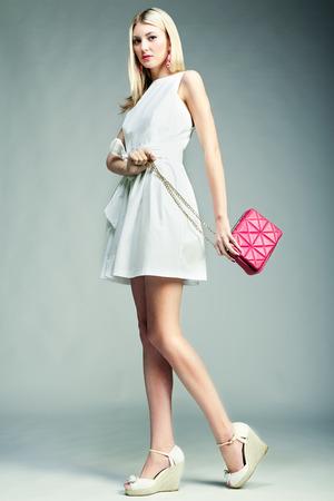 Fashion photo of young magnificent woman. Girl with handbag. Girl posing