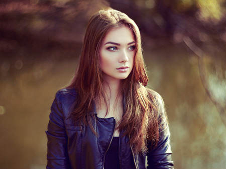 Portrait of young beautiful woman in leather jacket. Fashion photo