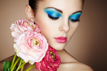Portrait of beautiful young woman with flowers. Perfect makeup. Perfect skin. Fashion photo