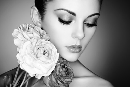 Foto de Portrait of beautiful young woman with flowers. Perfect makeup. Perfect skin. Fashion photo. Black and white - Imagen libre de derechos