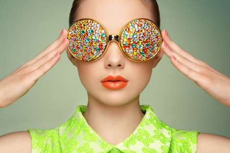 Photo pour Portrait of beautiful young woman with colored glasses. Beauty fashion. Perfect make-up. Colorful decoration. Jewelry - image libre de droit
