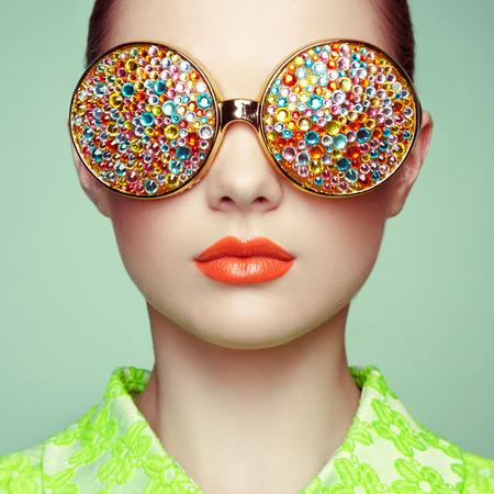 Foto de Portrait of beautiful young woman with colored glasses. Beauty fashion. Perfect make-up. Colorful decoration. Jewelry - Imagen libre de derechos