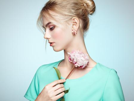 Photo pour Portrait of beautiful sensual woman with elegant hairstyle.  Perfect makeup. Blonde girl. Fashion photo. Flowers - image libre de droit