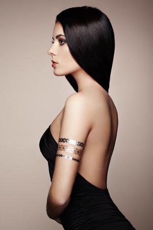Foto de Fashion portrait of elegant woman with magnificent hair. Brunette girl. Perfect make-up. Girl in elegant dress. Flash tattoo gold - Imagen libre de derechos