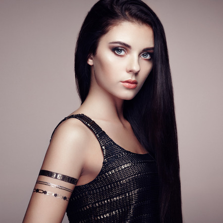 Photo pour Fashion portrait of elegant woman with magnificent hair. Brunette girl. Perfect make-up. Girl in elegant dress. Flash tattoo gold - image libre de droit