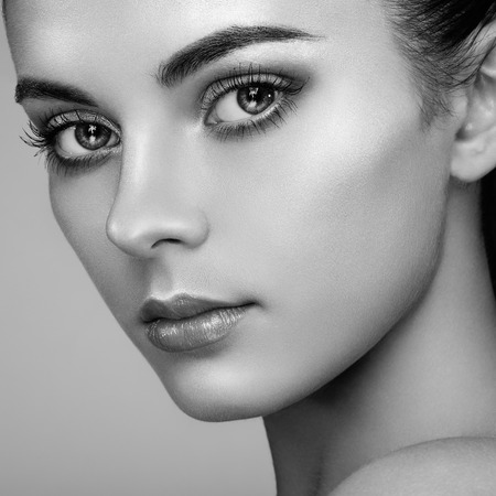 Beautiful woman face. Perfect makeup. Beauty fashion. Eyelashes. Cosmetic Eyeshadow. Highlighting. Black and white