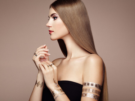 Photo pour Fashion portrait of elegant woman with magnificent hair. Blonde girl. Perfect make-up. Girl in elegant dress. Flash tattoo gold - image libre de droit