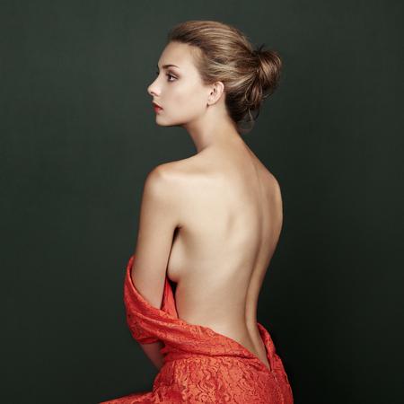 Foto de Fashion portrait of beautiful woman in elegant red dress. Hair and hairstyle. Beauy vintage style - Imagen libre de derechos