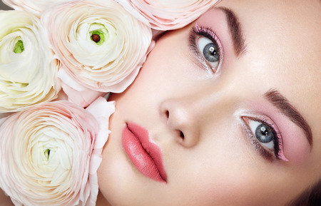 Photo pour Portrait of beautiful young woman with flowers. Brunette woman with luxury makeup. Perfect skin. Eyelashes. Cosmetic eyeshadow - image libre de droit