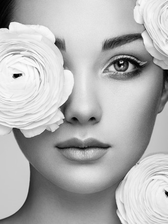 Photo for Portrait of beautiful young woman with flowers. Brunette woman with luxury makeup. Perfect skin. Eyelashes. Cosmetic eyeshadow - Royalty Free Image