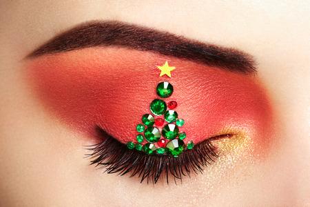 Photo for Eye girl makeover christmas tree. Winter christmas makeup. Beauty fashion. Eyelashes. Cosmetic Eyeshadow. Makeup detail. Creative woman holiday make-up - Royalty Free Image