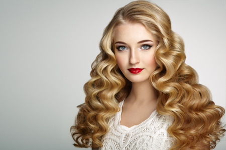 Beautiful girl with long wavy and shiny hair . Blonde woman with curly hairstyle. Perfect make-up. Fashion photo
