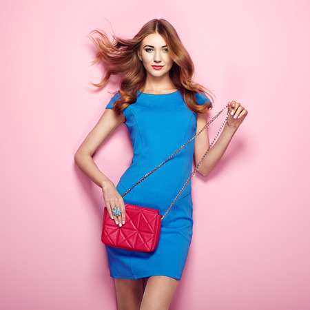 Foto de Blonde young woman in elegant blue dress. Girl posing on a pink background. Jewelry and hairstyle. Girl with red handbag. Fashion photo - Imagen libre de derechos
