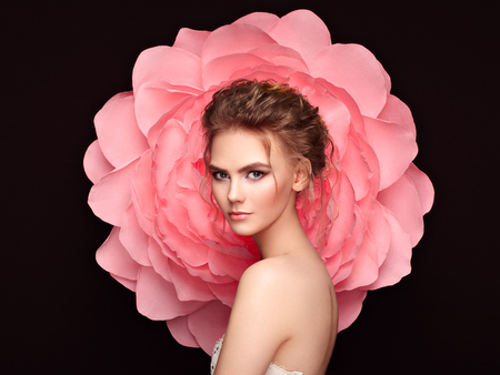 Photo pour Beautiful woman on the background of a large flower. Beauty summer model girl with pink peony. Young woman with elegant hairstyle and makeup. Fashion photo - image libre de droit