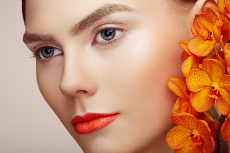Photo pour Portrait of beautiful young woman with orchid. Brunette woman with luxury makeup. Perfect skin. Eyelashes. Cosmetic eyeshadow. Orange flowers - image libre de droit
