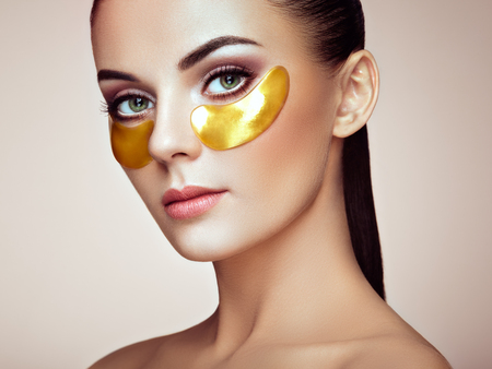 Photo pour Portrait of Beauty Woman with Eye Patches. Woman Beauty Face with Mask under Eyes. Beautiful Female with natural Makeup and Gold Cosmetics Collagen Patches on Fresh Facial Skin - image libre de droit