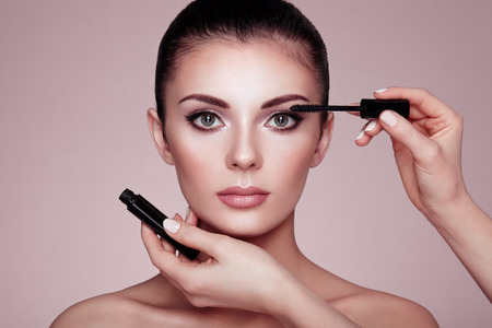 Photo for Beautiful Brunette Woman Paints the Eyelashes. Beautiful Woman Face. Makeup Detail. Beauty Girl with Perfect Skin. Make Up in process. Makeup Artis - Royalty Free Image