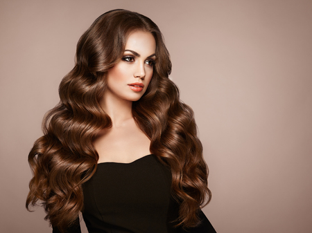 Photo pour Brunette Girl with Long Healthy and Shiny Curly Hair. Care and Beauty. Beautiful Model Woman with Wavy Hairstyle. Make-Up and Black Dress - image libre de droit