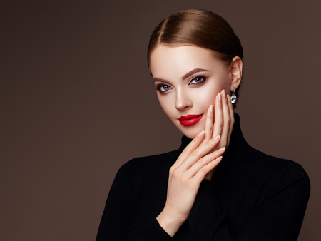 Foto de Beautiful Young Woman with Clean Fresh Skin. Perfect Makeup. Beauty Fashion. Red Lips. Cosmetic Eyeshadow. Smooth Hair. Girl in Black Turtleneck - Imagen libre de derechos