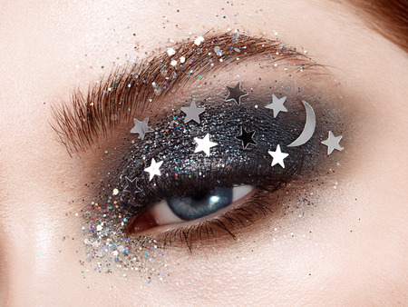 Photo pour Eye makeup woman with decorative stars. Perfect makeup. Beauty fashion. False Eyelashes. Cosmetic Eyeshadow. Make-up detail. Eyeliner. Creative make-up the night sky with stars - image libre de droit
