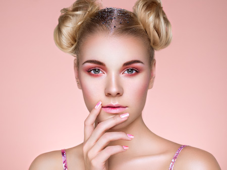 Foto de Blonde Girl with Elegant and shiny Hairstyle. Beautiful Model Woman with Curly Hairstyle. Care and Beauty Hair products. Nails and Manicure. Hair Curled into a Bun - Imagen libre de derechos