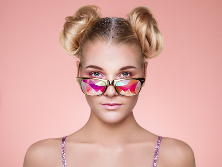 Foto de Portrait of Beautiful young Woman with Colored Glasses. Beauty Fashion. Perfect Make-up. Colorful Decoration. Hair Curled into a Bun - Imagen libre de derechos