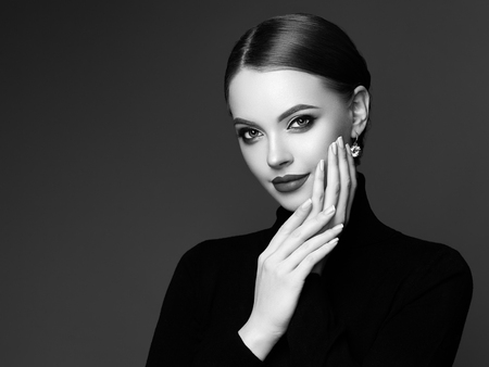 Photo pour Beautiful Young Woman with Clean Fresh Skin. Perfect Makeup. Beauty Fashion. Plump Lips. Cosmetic Eye shadow. Smooth Hair. Girl in Black Turtleneck. Black and white photo - image libre de droit