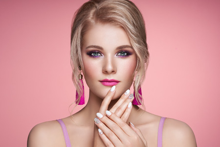 Photo pour Portrait Beautiful Blonde Woman with Jewelry. Model Girl with Pearl Manicure on Nails. Elegant Hairstyle. Precious Stones and Silver. Beauty and Fashion Accessories. Perfect Make-Up. Pink Background - image libre de droit