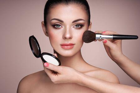 Photo pour Beautiful Woman applies Skin Tone with Brush. Beautiful Woman face. Perfect Makeup. Skincare Foundation. Brushes Makeup Artist - image libre de droit
