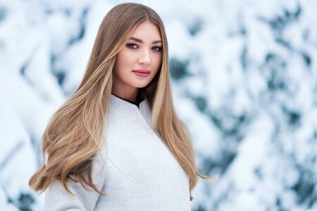 Photo pour Fashion young woman in the winter forest. Young elegant model in trendy white coat in nature. Blonde girl with long smooth hair - image libre de droit