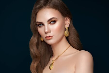 Photo pour Brunette girl with perfect makeup. Beautiful model woman with curly hairstyle. Care and beauty hair products. Lady with fashionable gold makeup. Model with jewelry on dark blue background - image libre de droit
