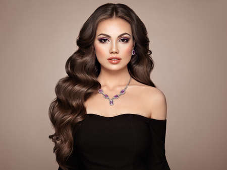 Photo pour Brunette Girl with Long Healthy and Shiny Curly Hair. Care and Beauty. Beautiful Model Woman with Wavy Hairstyle. MakeUp and Jewelry - image libre de droit