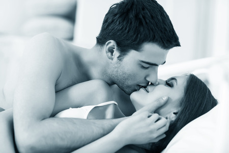 Photo pour Young passionate couple making love in bed - image libre de droit