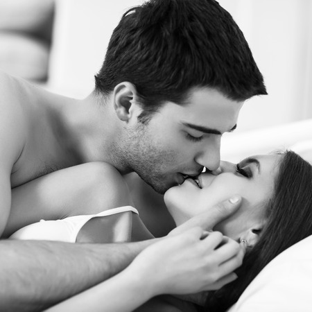 Young passionate couple making love in bed