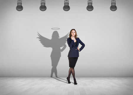 Businesswoman stands in the middle of the room with shadow on the wall