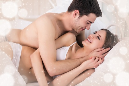 Photo pour Beautiful young loving couple lying in bed and looking at each other - image libre de droit