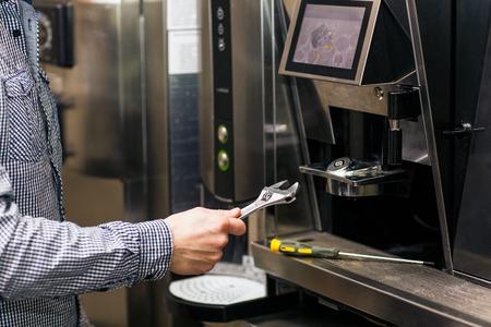 Photo pour Man going to prerare coffee maker machine with wrench - image libre de droit