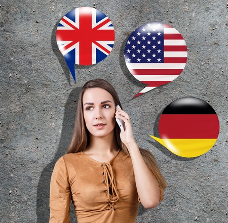 Young woman surrounded by bubbles with different countries flags. Learning of foreign languages concept.