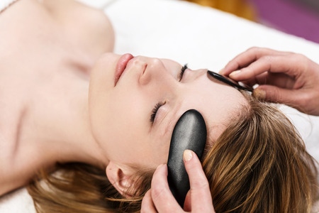 Photo for Young woman receiving facial massage with mineral stone - Royalty Free Image