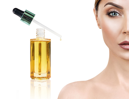 Photo pour Cosmetic oil applying on face of young woman. - image libre de droit