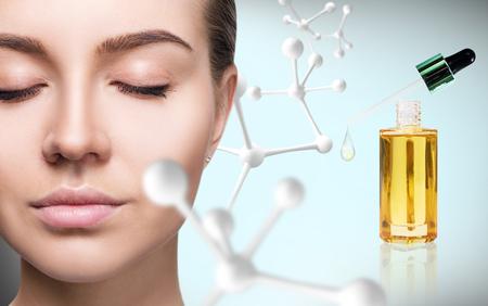 Photo pour Cosmetic primer oil near woman face with big molecule chain. - image libre de droit