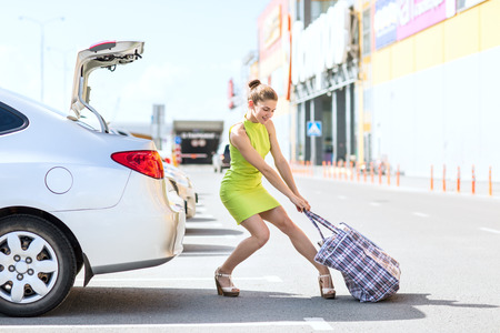 Photo pour Stylish woman houls heavy big bag to car trunk in summer day. - image libre de droit