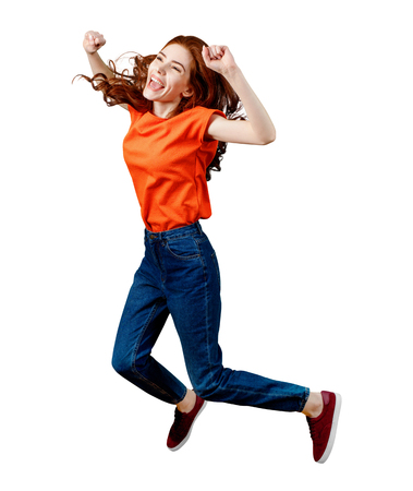 Photo pour Full length happy ginger woman in shirt and jeans jumping. - image libre de droit
