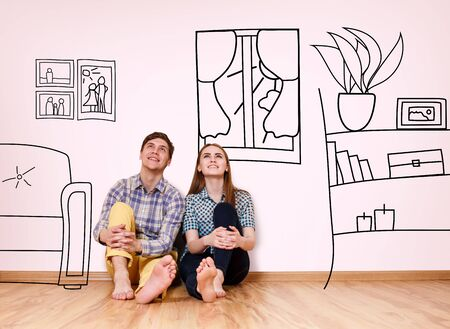 Photo pour Happy couple sitting in their new flat among painted furniture on the wall. - image libre de droit