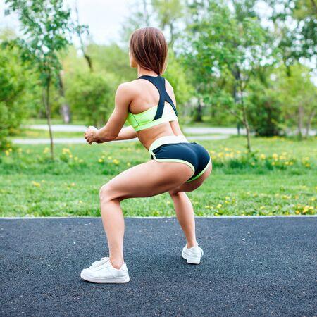 Photo pour Sports girl in sportswear squatting in the summer park. - image libre de droit