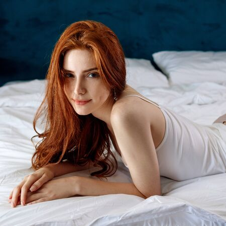 Photo for Young redheaded woman in white shirt lying on the bed. - Royalty Free Image