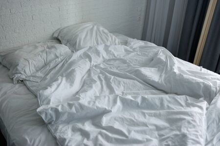 Photo for Untidy crumpled bed with white bedclothes. - Royalty Free Image