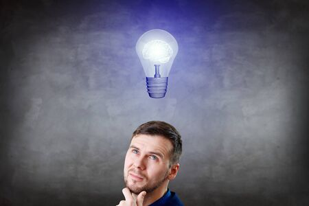 Photo for Businessman thinking and pointing finger on light bulb over head. - Royalty Free Image